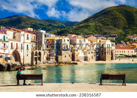 benches in front of old houses in the port of Cefalu, Sicily - stock photo