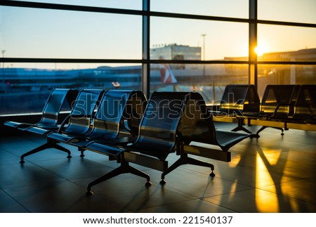 Benches in the departure hall of an airport during sunrise - stock photo