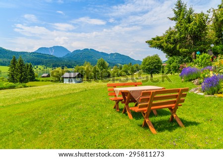 Benches with picnic table on green grass in alpine village on shore of Weissensee lake in summer landscape of Alps Mountains, Austria - stock photo