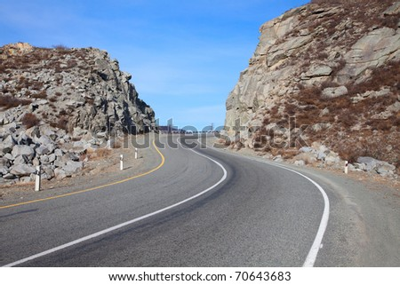 bend in the road in the mountains of autumn day - stock photo