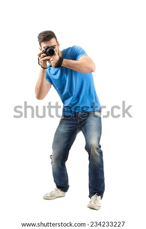Bend or lean young man taking photo with dslr looking at camera. Full body length portrait isolated over white background. - stock photo