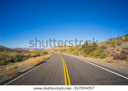 Bending highway road leading into the midst of the Mojave desert in southern California. - stock photo