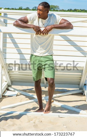 Bending over, both arms resting on a stick, a young handsome black guy is standing by a white wooden structure on the beach, looking around, relaxing. /Relaxing on the Beach  - stock photo