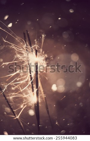 Bengal fire, sparkler and defocused falling snow, holiday background. - stock photo