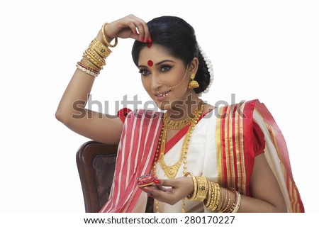 Bengali woman putting sindoor on her forehead - stock photo