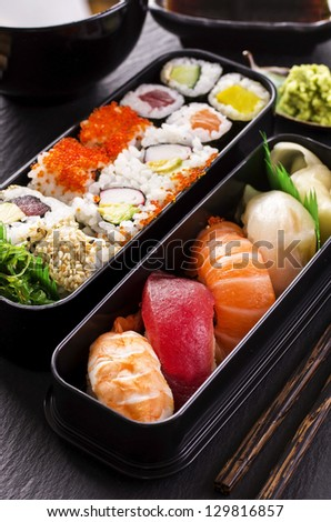 bento box with sushi and rolls - stock photo