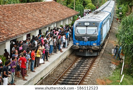 BENTOTA, SRI LANKA - 28 APR 2013: Train arrive to station with waiting people in Bentota, Sri Lanka. Trains are becoming more popular transport due to railway improvement by government. - stock photo