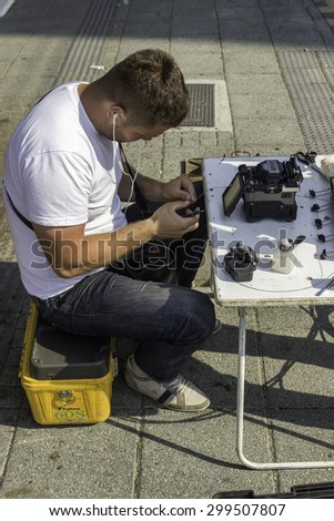 BEOGRAD, SERBIA - JULY 13, 2015:  Network technician on the street uses a fusion splicer to connect fiber optic cables. Cleave fiber optic cable. Selective focus and shallow dof. - stock photo