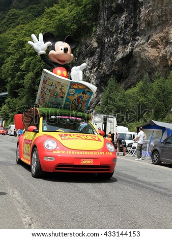 """BEOST,FRANCE-JUL 15: Mickey Mouse's car during the passing of the publicity caravan on the mountain pass Aubisque in the 13 stage of the """"Le Tour de France"""" on July 15 2011 - stock photo"""