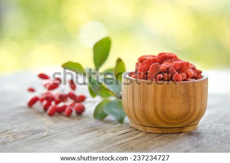 berberries and goji berries isolated on wooden table. - stock photo