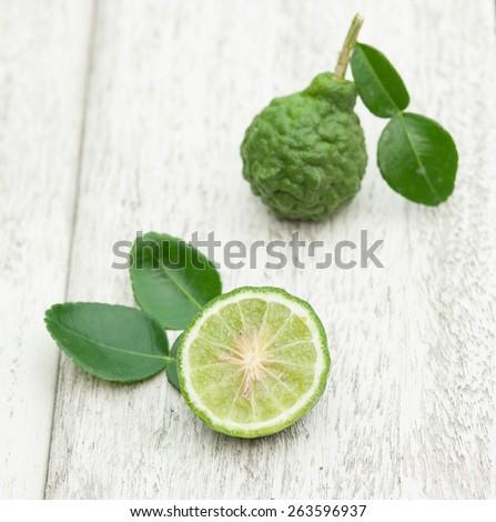 Bergamot fruit with green leafs on white wood background - stock photo
