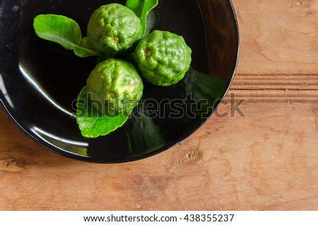 Bergamots with their leaves in black plate on the table - stock photo