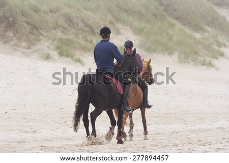 BERGEN AAN ZEE, NETHERLANDS - SEPTEMBER 11, 2005: Father and daughter riding horses on the beach. This beach is well known for the large dunes running parallel to the shoreline. - stock photo