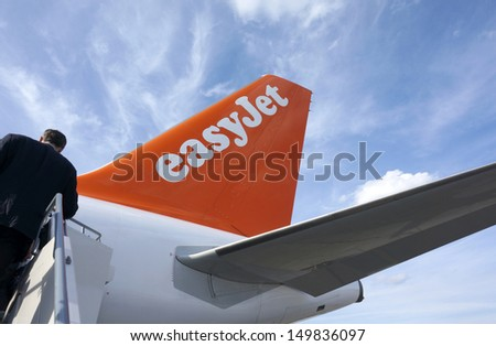 BERLIN - AUGUST 13: Business man boarding Easy Jet Flight from Berlin to London Gatwick, August 13, 2013 in Berlin, Germany - stock photo