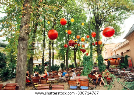 BERLIN, GERMANY - AUG 31: Lounge restaurant with people relaxing under green trees in park on August 31, 2015. Urban area of Berlin comprised 4 million people, 7th most populous in EU - stock photo