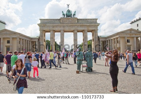 BERLIN, GERMANY, AUG 6 - Tourists in front of Brandenburg Tor, Berlin. It is a former city gate, rebuilt in the late 18th century and now one of the most known landmarks of Berlin. August 6, 2012. - stock photo