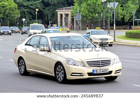 BERLIN, GERMANY - AUGUST 15, 2014: Beige taxi car Mercedes-Benz W212 E-class at the city street. - stock photo