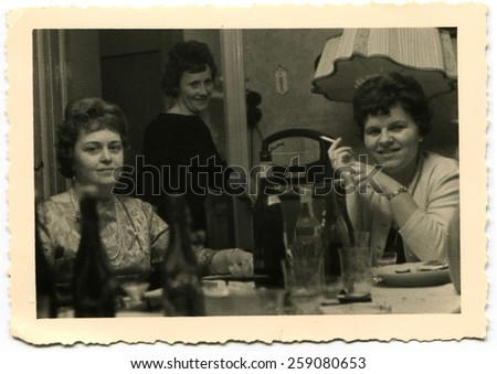 BERLIN, GERMANY - CIRCA 1960s: Three women posing at the festive table, on which stand the bottle of wine. One woman smokes a cigarette - stock photo