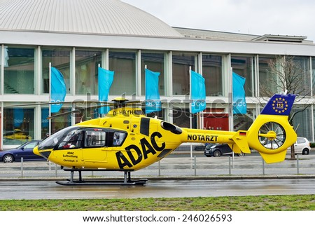 BERLIN, GERMANY-DECEMBER 23, 2014: German policeman protects ADAC rescue helicopter arrived for help on Alexanderplatz - stock photo