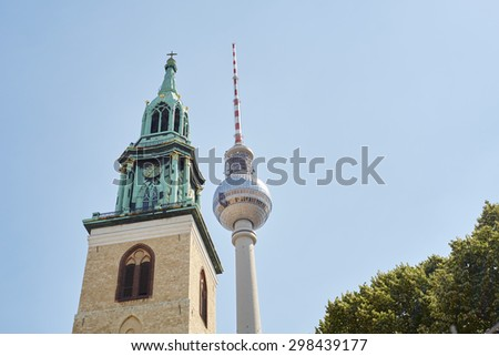 BERLIN, GERMANY - JULY 07: Low angle shot of TV tower in Alexanderplatz, with Saint Mary's Church tower in the foreground. July 07, 2015 in Berlin. - stock photo