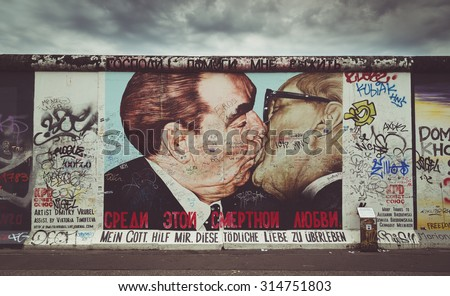 BERLIN, GERMANY - JULY 12: Street art graffiti painting 'The Kiss' by Dmitri Vrubel at famous East Side Gallery with retro vintage Instagram style filter effect on July 12, 2015 in Berlin, Germany. - stock photo