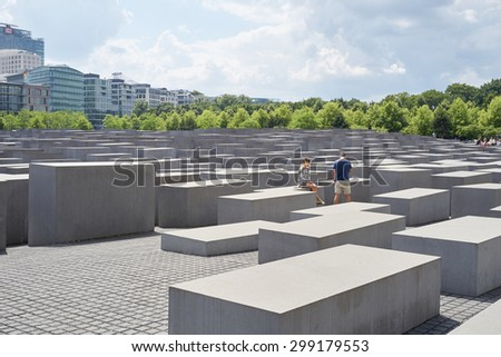 BERLIN, GERMANY - JULY 08: Young couple seated on stone block at the Memorial to the Murdered Jews of Europe. July 08, 2015 in Berlin. - stock photo