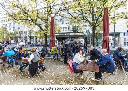BERLIN, GERMANY - OCT 27, 2014: old vintage Kiosk name is renamed to oval office and people enjoy on tables the autumn summer in Berlin, Germany. - stock photo