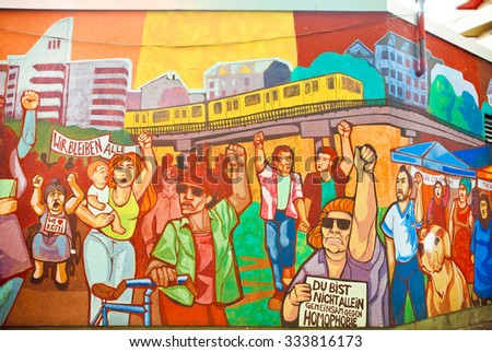 BERLIN, GERMANY - SEPT 1, 2015: Artwork on wall graffiti with crowd of immigrants protesting for rights on Septemper 1, 2015. Urban area of Berlin comprised 4 million people, 7th most populous in EU - stock photo