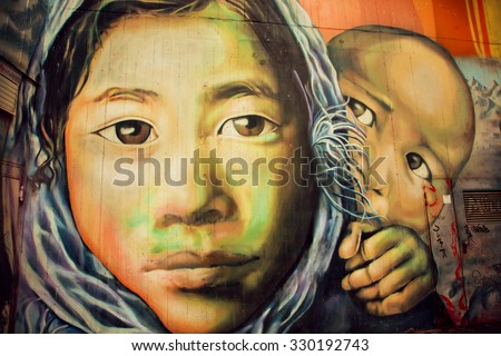 BERLIN, GERMANY - SEPT 2, 2015: Graffiti with poor refugees family on street art wall on Septemper 2, 2015. Urban area of Berlin comprised 4 million people, 7th most populous in EU - stock photo
