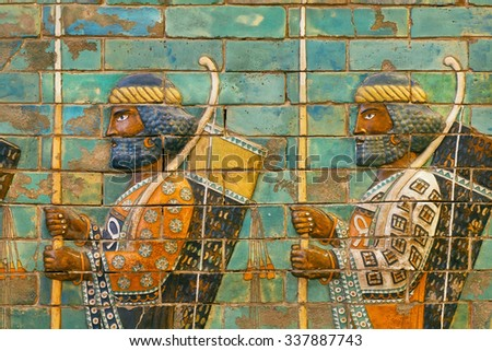 BERLIN, GERMANY - SEPT 2, 2015: Two soldiers of historical empire with bows and spears, ceramic patterned wall of city Babylon on Septemper 2, 2015. Artifact of Iraq saved by Pergamon Museum in Berlin - stock photo