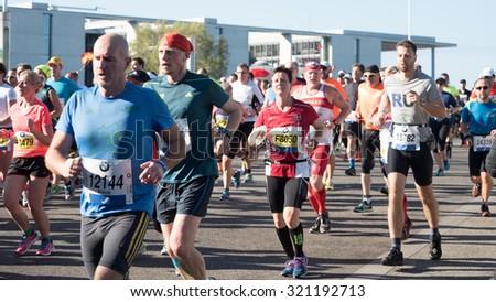 Berlin, Germany - September 27, 2015: Marathon runners in Reinhardstrasse, near Reichstag Building - stock photo