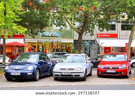 BERLIN, GERMANY - SEPTEMBER 12, 2013: Parking of a small city Volkswagen cars at the city street. - stock photo