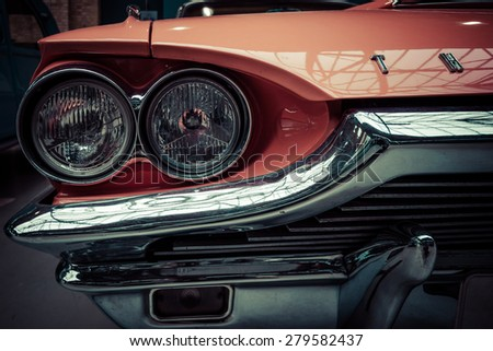 BERLIN - MAY 10, 2015: Headlamp of a large personal luxury car Ford Thunderbird 390 Coupe (second generation), 1964. Stylization. Vintage toning. 28th Berlin-Brandenburg Oldtimer Day - stock photo