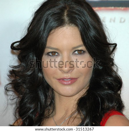 """BERLIN, OCTOBER 2: Catherine Zeta-Jones  looks into the camera at a photocall for heir upcoming film """"Zorro"""" in Berlin on October 2, 2005. - stock photo"""