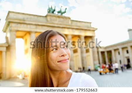 Berlin people - woman at Brandenburg Gate or Brandenburger Tor, smiling happy in Berlin, Germany. Beautiful multiracial Asian Caucasian woman looking to side during travel in Europe. - stock photo