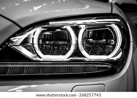 BERLIN - SEPTEMBER 09, 2012: Showroom. Headlamp of a Grand tourer / executive coupe BMW 640i Gran Coupe (F06). Close-up. Black and white. Produced since 2012. - stock photo