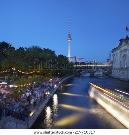Berlin, strand bar on Spree river at night, people dancing, boat passing - stock photo