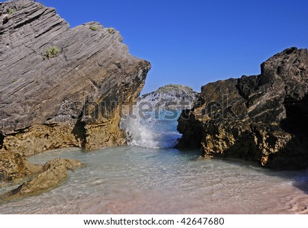 Bermuda's Horseshoe Bay beach during a hot summer day.  Photo includes the sky, rocks, pink sand and a wave rolling in. - stock photo