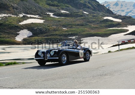 BERNINA PASS, SWITZERLAND - JUNE 14: A black Jaguar XK 120 OTS takes part to the Summer Marathon classic car race on June 14, 2014 at Bernina Pass. This car was built in 1950 - stock photo
