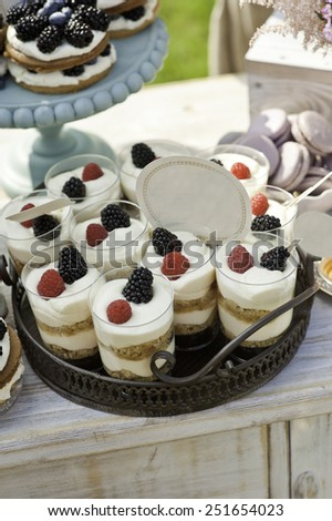 Berries desserts with cream and biscuits in glasses - stock photo