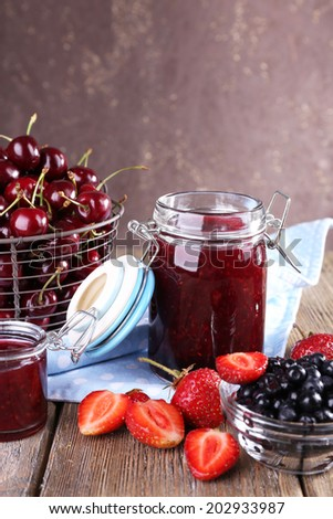 Berries jam in glass jar on table, close-up - stock photo