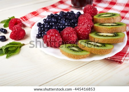 Berries on plate.Blueberry,raspberry,kiwi.Vitamin A. Vitamin C.Checkered napkin.On white wooden table.Healthy lifestyle.Diet and weight loss concept. - stock photo