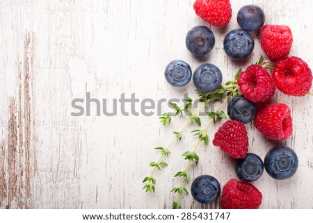 Berries on White Wooden Background. Summer or Spring Organic Berry over Wood. Raspberries, Blueberry and thyme. Healthy food, Gardening, Harvest Concept. Copy space. - stock photo