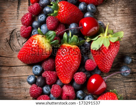 Berries on Wooden Background. Spring Organic Berry over Wood. Strawberries, Raspberries, Blueberry and Cherry. Agriculture, Gardening, Harvest Concept. Gardening. Vitamin. Diet - stock photo