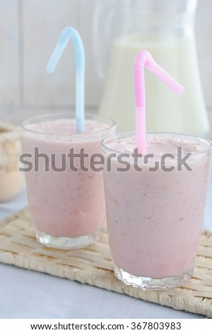 Berries smoothies in glasses and milk in jug on rustic wooden table - stock photo
