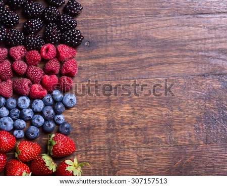 Berries (strawberry , raspberry , blueberries &  blackberries )  on wooden background - stock photo