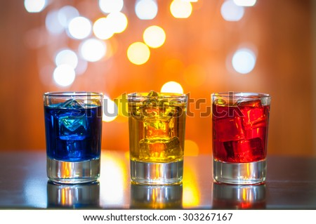 Berry alcoholic drink into small glasses on bar desk with magic illumination bokeh background. - stock photo