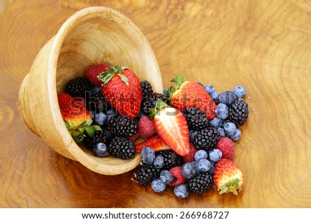 berry assortment - raspberries, blackberries, strawberries, blueberry on a wooden background - stock photo