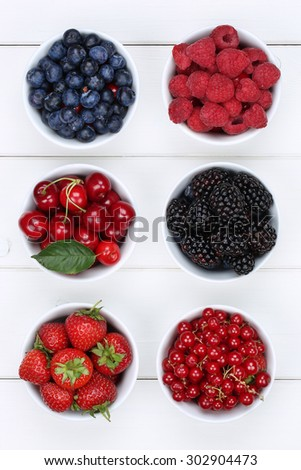 Berry fruits in bowls with strawberries, blueberries, red currants, cherries, raspberries and blackberries from above - stock photo