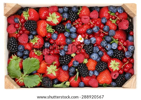 Berry fruits in wooden box with strawberries, blueberries, red currants, cherries, raspberries and blackberries - stock photo